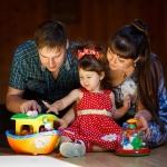 фотография девочка играет с мамой и папой