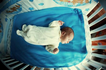 Фотография двухнедельного младенца в кроватке
